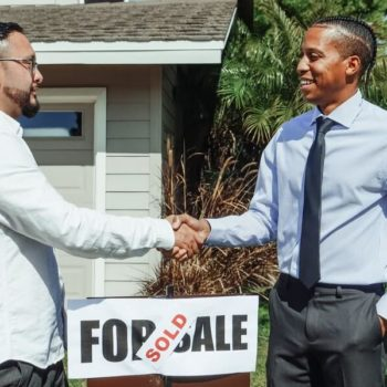 people shaking hands over a for sale sign